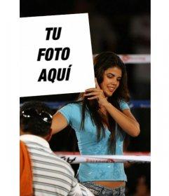 En este fotomontaje, una hermosa chica con una camiseta azul, sonríe mientras sujeta tu foto a modo de cartel en el descanso de un combate de boxeo, Como anunciando al próximo boxeador