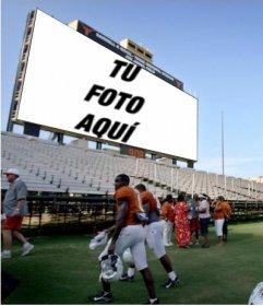 En este fotomontaje, tu fotografía aparecerá en la gran pantalla de un estadio de fútbol americano, donde hay gente, jugadores entre ellos